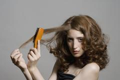 A young woman brushing her hair - stock photo