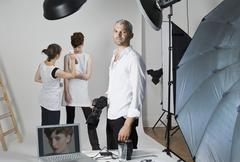 A photographer, model and make-up artist on set of a fashion shoot Stock Photos