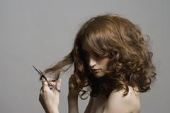 A young woman holding scissors and cutting her hair Stock Photos