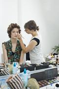 A make-up artist applying make-up on a model - stock photo