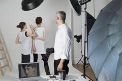 A photographer, model and make-up artist on set of a fashion shoot - stock photo