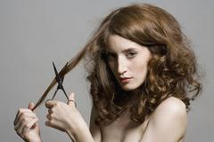 Portrait of a young woman holding scissors to her hair Stock Photos