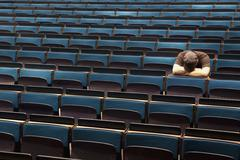 A man sitting in an auditorium with his head resting in his arms Stock Photos
