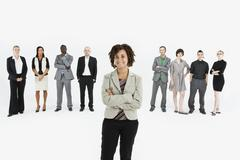 A young professional standing in front of a row of business people - stock photo