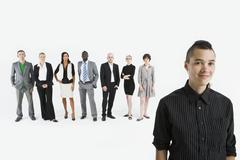 A young professional in front of a row of business people - stock photo