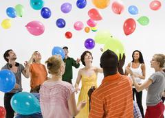 A group of men and women reaching for floating balloons - stock photo