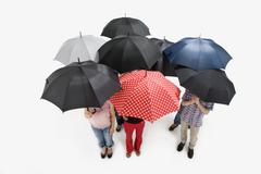 Group of men and women standing under umbrellas Stock Photos