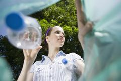 A woman throwing a plastic bottle away - stock photo