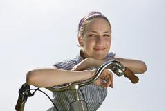 A young woman leaning on bicycle handlebars - stock photo