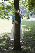 A young woman hugging a tree, obscured face Stock Photos