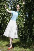 A young woman standing amongst lush foliage Stock Photos