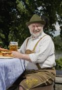 A traditionally clothed German man in a beer garden - stock photo