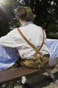 A traditionally clothed German man in a beer garden, rear view - stock photo