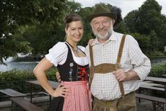 A traditionally clothed German man and woman in a beer garden, portrait - stock photo