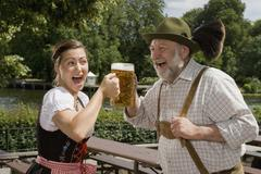 A traditionally clothed German man and woman in a beer garden toasting glasses - stock photo