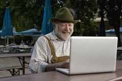 A traditionally clothed German man in a beer garden using a laptop Stock Photos
