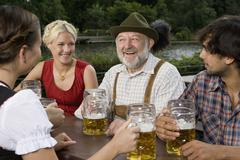 Four people in a beer garden - stock photo