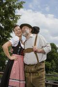 A traditionally clothed German man and woman in a beer garden - stock photo