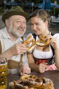 A traditionally clothed German man and woman in a beer garden holding pretzels Stock Photos