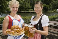 Two traditionally clothed German women serving pretzels and beer in a beer Stock Photos