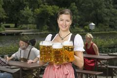 A traditionally clothed German woman serving beer in a beer garden - stock photo