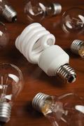 An energy saving light bulb among a group of filament light bulbs Stock Photos