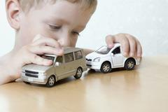 A boy playing with two toy cars Stock Photos