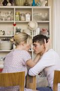 A young passionate couple sitting in a domestic kitchen - stock photo