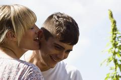A young woman playfully licking a young man's ear Stock Photos