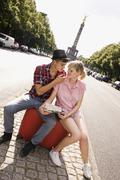 A young couple with a suitcase and a map with the Berlin Victory Column in - stock photo