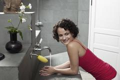 A woman using a sink in a health spa bathroom Stock Photos