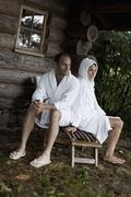A couple relaxing outside the sauna at a health spa - stock photo