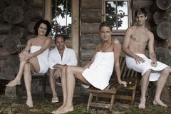 Four people relaxing outside the sauna at a health spa Stock Photos