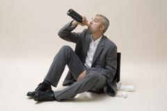 A businessman drinking a bottle of wine Stock Photos