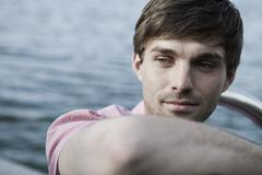 A man relaxing by a lake, head and shoulders - stock photo