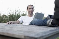 A man sitting at an outdoor table reading a magazine, non-urban scene Stock Photos