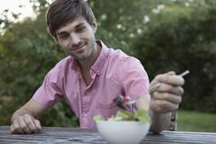 A man eating at a table outdoors, non-urban scene - stock photo