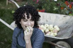A woman taking a bite from a freshly picked apple - stock photo