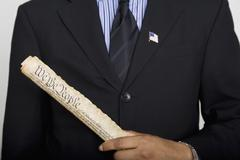 Midsection of a man holding a copy of the US Constitution - stock photo