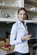 A standing in the kitchen and holding a piece of red pepper - stock photo