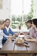 Friends sitting at a dinning table together - stock photo