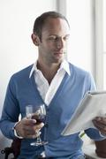 A man drinking a glass of wine and reading a magazine Stock Photos