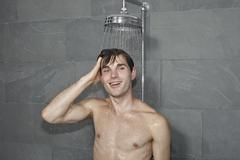 A man standing underneath a shower Stock Photos