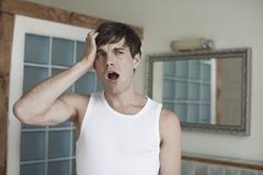 Mies haukottelee kylpyhuoneessa Kuvituskuvat