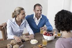 A group of friends sitting at the dining table together Stock Photos