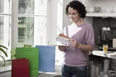 A woman standing next to gift bags and looking at cards Stock Photos