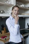 A woman eating a piece of red pepper in the kitchen - stock photo
