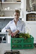 A woman in the kitchen with a vegetable basket Stock Photos