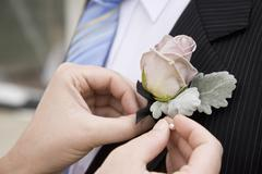 Detail of a woman pinning a corsage to a jacket lapel - stock photo