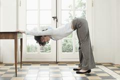 A businesswoman stretching against a table - stock photo